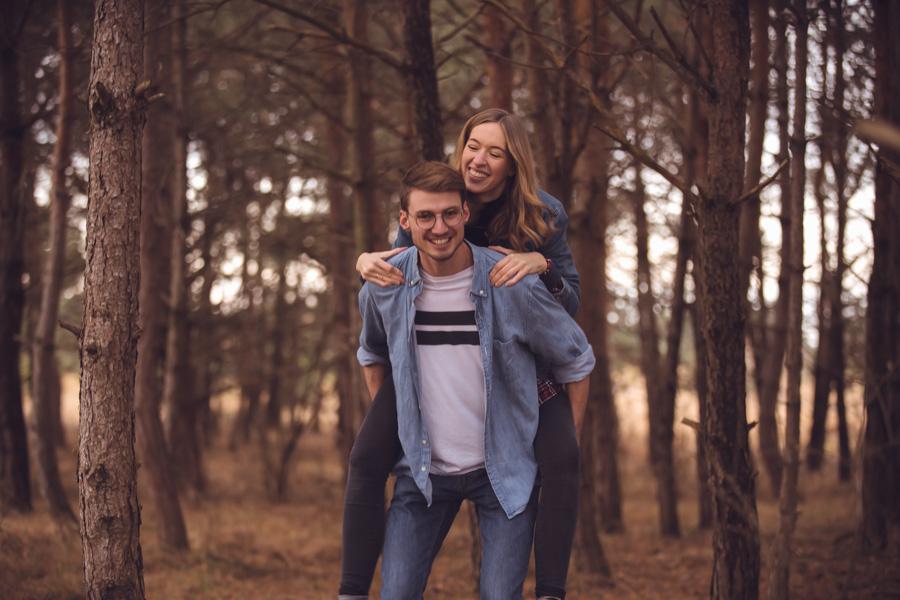 Verliebtes Paar huckepack beim Fotoshooting im Wald